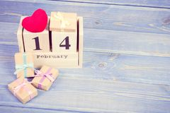 Εκλεκτής ποιότητας φωτογραφία, ημερολόγιο κύβων με στις 14 Φεβρουαρίου ημερομηνίας, δώρα και κόκκινο διάστημα αντιγράφων καρδιών  Στοκ Εικόνα