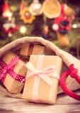 Εκλεκτής ποιότητας φωτογραφία, τυλιγμένα δώρα με τις κορδέλλες στο σάκο για τα Χριστούγεννα και χριστουγεννιάτικο δέντρο με τη δι Στοκ Φωτογραφία
