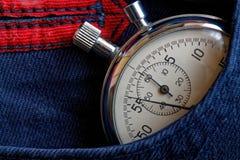 Εκλεκτής ποιότητας χρονόμετρο με διακόπτη αντικών, στη σκούρο μπλε τσέπη τζιν, χρόνος μέτρου αξίας, παλαιό λεπτό βελών ρολογιών,  Στοκ Εικόνες