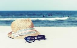 Εκλεκτής ποιότητας ψάθινο καπέλο αχύρου και μαύρα γυαλιά ήλιων σε μια τροπική παραλία, θερινή έννοια στοκ φωτογραφία με δικαίωμα ελεύθερης χρήσης