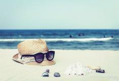 Εκλεκτής ποιότητας ψάθινο καπέλο αχύρου και μαύρα γυαλιά ήλιων σε μια τροπική παραλία, θερινή έννοια στοκ εικόνα