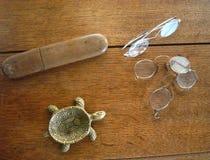 Εκλεκτής ποιότητας ashtray χελωνών, γυαλιά, και κιβώτιο γυαλιών σε μια ξύλινη επιφάνεια στοκ φωτογραφία