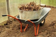 Εκλεκτής ποιότητας wheelbarrow κινηματογραφήσεων σε πρώτο πλάνο σύνολο της χλόης στο υπόβαθρο κήπων άνοιξη Στοκ Εικόνες