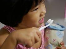 Εκλεκτική εστίαση λίγης ασιατικής οδοντόβουρτσας και της απόλαυσης εκμετάλλευσης κοριτσάκι βουρτσίζοντας τα δόντια της από μόνη τ στοκ φωτογραφία
