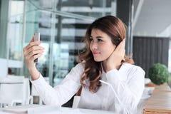 Εκλεκτική εστίαση στο κινητό έξυπνο τηλέφωνο στα χέρια της ελκυστικής νέας ασιατικής γυναίκας που παίρνει τη φωτογραφία ή selfie  στοκ φωτογραφία με δικαίωμα ελεύθερης χρήσης