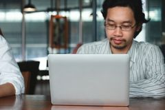 Εκλεκτική εστίαση στο lap-top με το ασιατικό άτομο στο υπόβαθρο στοκ εικόνα με δικαίωμα ελεύθερης χρήσης