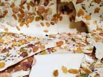 Εκλεκτική εστίαση του φραγμού σοκολάτας γάλακτος με τα αμύγδαλα, τις σταφίδες, το καρύδι και τα σιτάρια ως υπόβαθρο στοκ φωτογραφίες