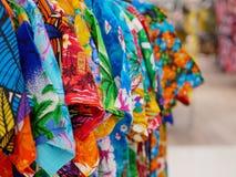 Εκλεκτική εστίαση των ζωηρών ζωηρόχρωμων μπλουζών στις κρεμάστρες για την πώληση σε μια λεωφόρο αγορών στοκ φωτογραφίες με δικαίωμα ελεύθερης χρήσης