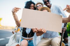 εκλεκτική εστίαση των πολυπολιτισμικών φίλων που κρατούν το κενό χαρτόνι ενώ Στοκ Εικόνες