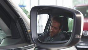 Εκλεκτικό focua σε έναν δευτερεύοντα καθρέφτη ενός αυτοκινήτου, ευτυχής χαλάρωση ατόμων σε ένα νέο αυτοκίνητο απόθεμα βίντεο