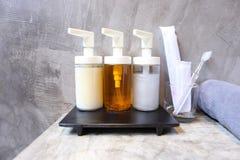 Εκλεκτικό focuse του μπουκαλιού γυαλιού αντλιών με το υγρούς σαπούνι, το σαμπουάν, τον αφρό λουτρών και τα εξαρτήματα στο λουτρό  στοκ φωτογραφίες