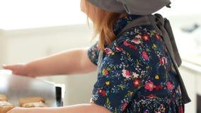 Εκμετάλλευση αρτοποιών μικρών κοριτσιών στα χέρια που ψήνει το φύλλο με τα σπιτικά μπισκότα απόθεμα βίντεο
