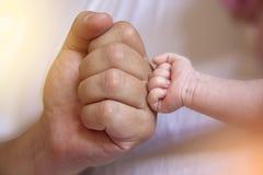 Εκμετάλλευση γονέα στα πόδια χεριών του νεογέννητου μωρού στοκ φωτογραφίες με δικαίωμα ελεύθερης χρήσης