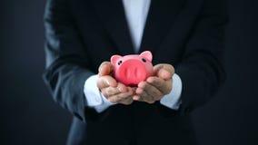 Εκμετάλλευση επιχειρηματιών piggybank στα χέρια, επένδυση επιχείρησης, οικονομικός σύμβουλος απόθεμα βίντεο
