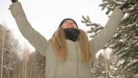 Εκμετάλλευση νέων κοριτσιών στο χιόνι χεριών Το κορίτσι φυσά και ρίχνει επάνω στο χιόνι στο χειμερινό δάσος απόθεμα βίντεο
