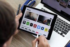 Εκμετάλλευση χεριών ατόμων iPad και MacBook με App το κατάστημα στην οθόνη Στοκ φωτογραφίες με δικαίωμα ελεύθερης χρήσης