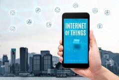 Εκμετάλλευση χεριών κινητή με Διαδίκτυο της λέξης πραγμάτων iot στην οθόνη στοκ εικόνα