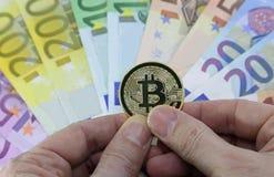 Εκμετάλλευση χεριών με ένα χρυσό bitcoin και ευρωπαϊκά τραπεζογραμμάτια στοκ εικόνες