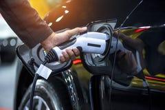Εκμετάλλευση χεριών που φορτίζει την ηλεκτρική μπαταρία αυτοκινήτων στοκ φωτογραφίες