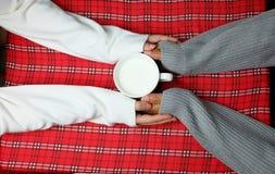 Εκμετάλλευση χεριών στο χειμώνα με το θερμό ποτό στο κόκκινο επιτραπέζιο ύφασμα Στοκ εικόνες με δικαίωμα ελεύθερης χρήσης