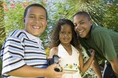 Εκμετάλλευση αγοριών (7-9) camcorder με τη νεώτερη αδελφή (5-6) και το παλαιότερο πορτρέτο αδελφών (10-12). Στοκ εικόνα με δικαίωμα ελεύθερης χρήσης