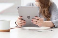 Εκμετάλλευση γυναικών υπέρ διαστημικό στον γκρίζο iPad χεριών νέο Στοκ φωτογραφία με δικαίωμα ελεύθερης χρήσης