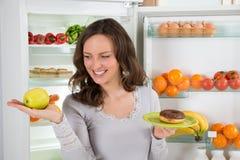 Εκμετάλλευση η πράσινη Apple γυναικών και doughnut Στοκ φωτογραφία με δικαίωμα ελεύθερης χρήσης