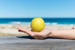 Εκμετάλλευση η πράσινη Apple χεριών γυναίκας στο ξύλο στην παραλία Στοκ Εικόνα
