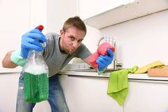 Εκμετάλλευση νεαρών άνδρων που καθαρίζει καθαριστικό εγχώριων κουζινών πλύσης ψεκασμού και σφουγγαριών καθαρό στην πίεση Στοκ Φωτογραφίες