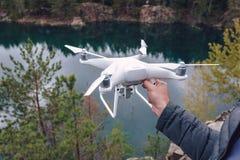 Εκμετάλλευση χειριστών quadrocopter στα χέρια του πριν από την απογείωση Τηλεκατευθυνόμενο εναέριο copter στοκ φωτογραφία