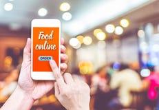 Εκμετάλλευση χεριών κινητή με τα τρόφιμα διαταγής on-line με το εστιατόριο θαμπάδων στοκ εικόνα με δικαίωμα ελεύθερης χρήσης
