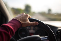 Εκμετάλλευση χεριών στο μαύρο τιμόνι οδηγώντας στο αυτοκίνητο Στοκ Φωτογραφία