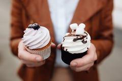 Εκμετάλλευση χεριών cupcake που διακοσμείται με το βατόμουρο Στοκ εικόνα με δικαίωμα ελεύθερης χρήσης