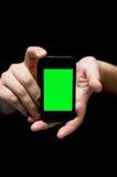 Εκμετάλλευση Smartphone χεριών, που παρουσιάζει κενή πράσινη οθόνη Στοκ Φωτογραφία