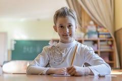 εκπαίδευση και σχολική έννοια - λίγο κορίτσι σπουδαστών που γράφει στο σημειωματάριο στο σχολείο στοκ φωτογραφία