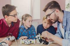 Εκπαίδευση ΜΙΣΧΩΝ Παιδιά που δημιουργούν τα ρομπότ με το δάσκαλο Στοκ Εικόνες