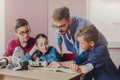 Εκπαίδευση ΜΙΣΧΩΝ Παιδιά που δημιουργούν τα ρομπότ με το δάσκαλο Στοκ Φωτογραφίες