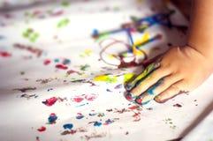 Εκπαίδευση, σχολείο, τέχνη και painitng έννοια - μικρό κορίτσι που παρουσιάζει χρωματισμένα χέρια στοκ φωτογραφία