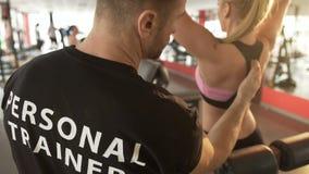 Εκπαιδευτής γυμναστικής που εξηγεί pull-down την τεχνική στη γυναίκα εκπαιδευόμενος, επαγγελματική βοήθεια φιλμ μικρού μήκους