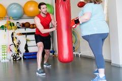 Εκπαιδευτής ικανότητας που βοηθά την υπέρβαρη γυναίκα στοκ εικόνα