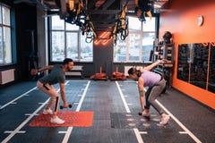 Εκπαιδευτής και υπέρβαρος πελάτης που κάνουν τις ασκήσεις με τα barbells στοκ εικόνες