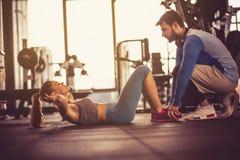 Εκπαιδευτής που βοηθά τη γυναίκα στην άσκηση στοκ εικόνα με δικαίωμα ελεύθερης χρήσης