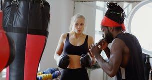Εκπαιδευτής που βοηθά το θηλυκό μπόξερ στο στούντιο 4k ικανότητας απόθεμα βίντεο