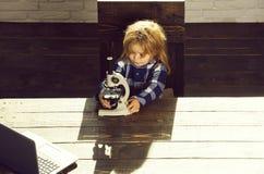 Εκπαιδευτική έννοια, σπουδαστής αγοριών που μελετά στον εργασιακό χώρο με το μικροσκόπιο, lap-top στοκ εικόνα με δικαίωμα ελεύθερης χρήσης