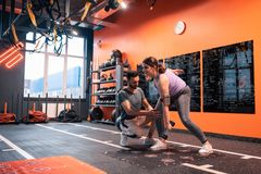 Εκπαιδευτική ελέγχοντας γυναίκα ικανότητας που κάνει τις ασκήσεις με τα barbells στοκ φωτογραφία