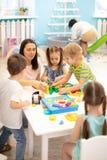 Εκπαιδευτικός που βοηθά τα παιδιά που παίζουν με τον κατασκευαστή φραγμών στη φύλαξη στοκ εικόνες με δικαίωμα ελεύθερης χρήσης
