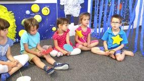 Εκπαιδευτικός που περιβάλλεται από τα παιδιά στον παιδικό σταθμό απόθεμα βίντεο