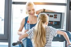 Εκπαιδευτής γυναικών που εξετάζει το μικρό κορίτσι workout treadmill Στοκ Εικόνα