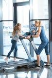 Εκπαιδευτής γυναικών που εξετάζει το μικρό κορίτσι workout treadmill Στοκ φωτογραφίες με δικαίωμα ελεύθερης χρήσης