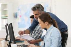 Εκπαιδευτής με τους οικότροφους που εργάζονται στον υπολογιστή γραφείου Στοκ Εικόνες